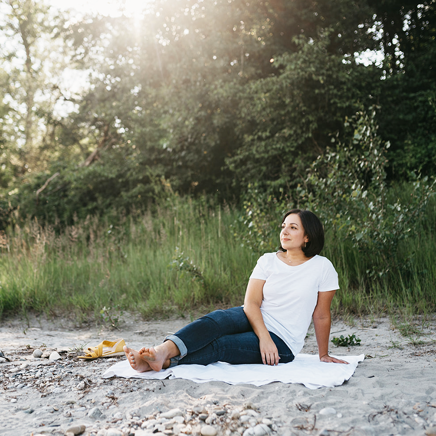 Karina the Personal Brand Architect in white t-shirt and jeans sitting on a river bank